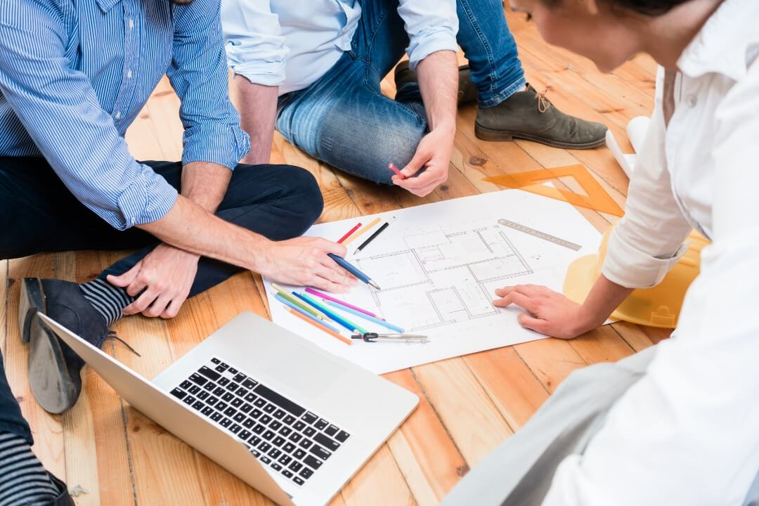 group of people working on a floor plan