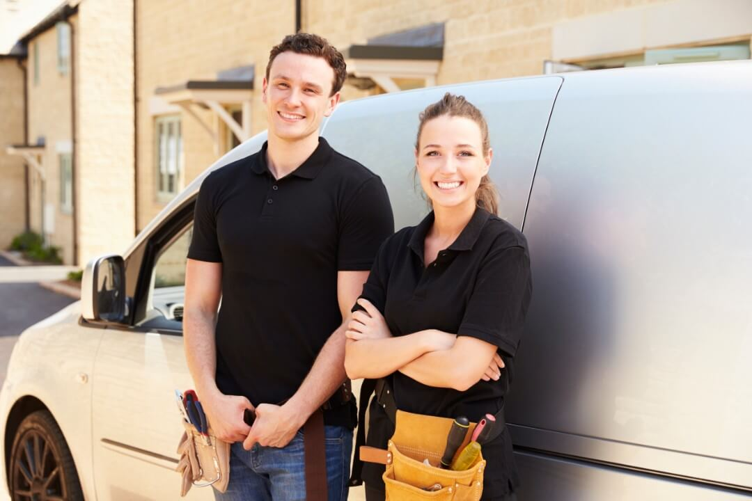 male and female tradespeople smiling in front of van